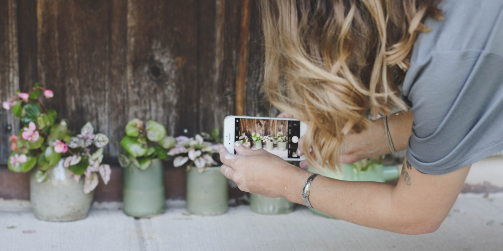 Woman taking a photo of potted plants with a smart phone | Retail Shift Podcast Episode 1: Shifting the Customer Service Role from Seller to Entertainer | Hosted by Chris Guillot of Merchant Method | Subscribe at merchant.tips/podcast